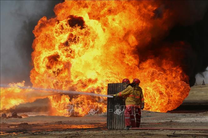 Nhân viên cứu hỏa Iraq nỗ lực khống chế đám cháy tại mỏ dầu Khabbaz sau vụ tấn công do các phần tử khủng bố IS tiến hành ngày 1-6-2016. Ảnh tư liệu: AFP/TTXVN