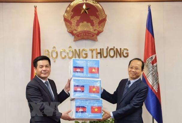 Bộ trưởng Công Thương Nguyễn Hồng Diên trao tượng trưng 20.000 khẩu trang phòng, chống dịch COVID-19 cho Đại sứ Campuchia. Ảnh: Trần Việt/TTXVN