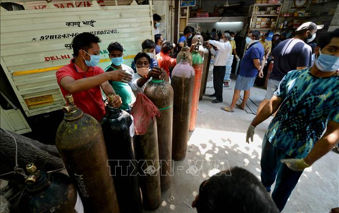 Người dân chờ bơm đầy bình oxy để cung cấp cho bệnh nhân COVID-19 tại New Delhi, Ấn Độ, ngày 5-5-2021. Ảnh: THX/TTXVN