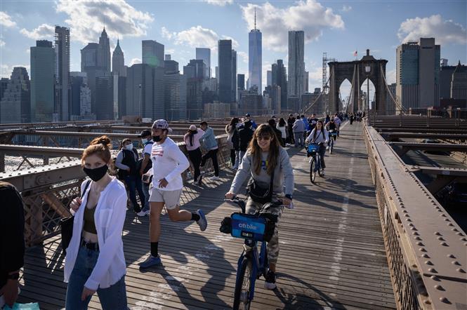 Người dân di chuyển trên cầu Brooklyn ở New York, Mỹ, ngày 25-4-2021. Ảnh: AFP/ TTXVN