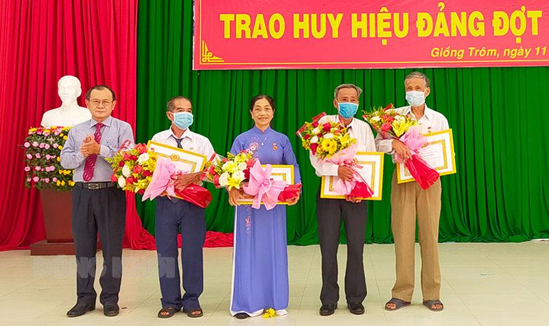 Phó chủ tịch Thường trực HĐND tỉnh Huỳnh Quang Triệu trao huy hiệu đảng cho đảng viên.