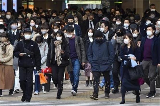 Người dân đeo khẩu trang phòng dịch COVID-19 tại Tokyo, Nhật Bản. Ảnh: Kyodo/TTXVN