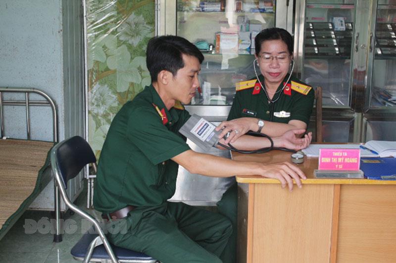 Thiếu tá Đinh Thị Mỹ Hoàng khám bệnh cho bộ đội.