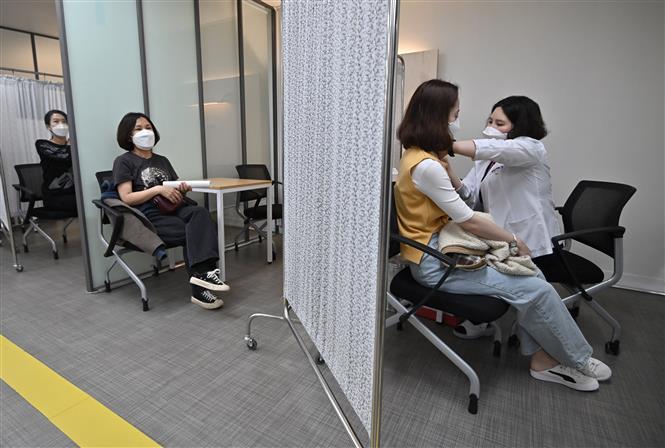 Nhân viên y tế tiêm vaccine phòng COVID cho người dân tại Seoul, Hàn Quốc, ngày 20-3-2021. Ảnh: AFP/TTXVN