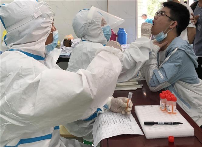 Nhân viên y tế lấy mẫu xét nghiệm COVID-19 tại tỉnh An Huy, Trung Quốc, ngày 14-5-2021. Ảnh: THX/TTXVN