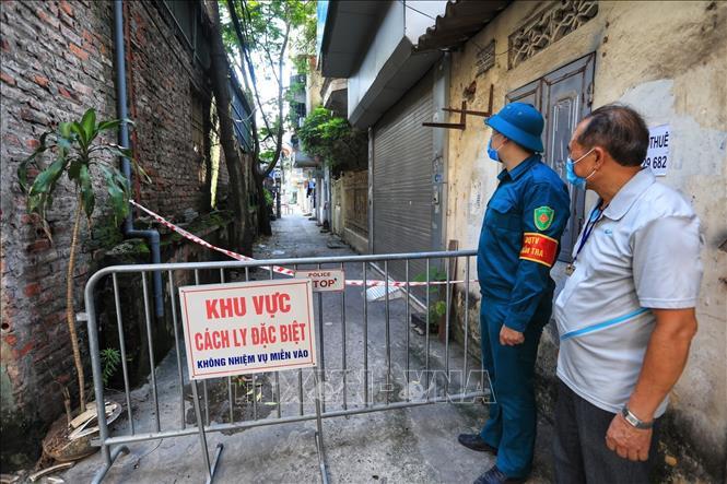 Lực lượng chức năng làm nhiệm vụ tại khu vực cách ly do có người bị nhiễm SARS-CoV-2. Ảnh: Phan Tuấn Anh/TTXVN