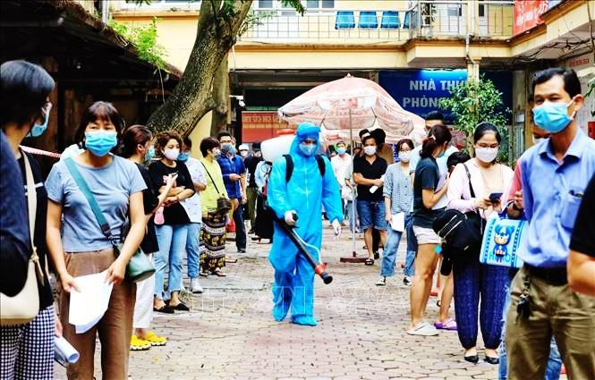 Nhân viên y tế quận Hoàn Kiếm tiến hành lấy mẫu xét nghiệm COVID-19 cho người dân từ Đà Nẵng trở về. Ảnh: TTXVN