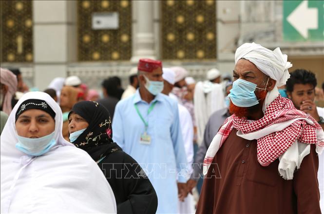 Người dân đeo khẩu trang phòng lây nhiễm COVID-19 tại Mecca, Saudi Arabia, ngày 13-3-2020. Ảnh: AFP/TTXVN