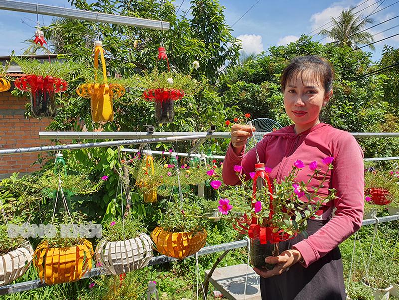 Chị Kim Chi với các chậu hoa treo làm từ chai nhựa tái chế.