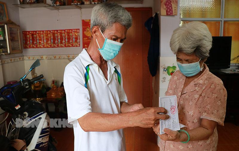 Ông Văn Tiết Thanh phát thẻ cử tri cho một gia đình người Hoa ở hẻm Hòa Bình.