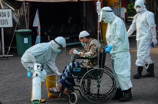 Nhân viên y tế chuyển bệnh nhân COVID-19 tới bệnh viện ở Surabaya, Đông Java, Indonesia, ngày 13-5-2021. Ảnh: THX/ TTXVN
