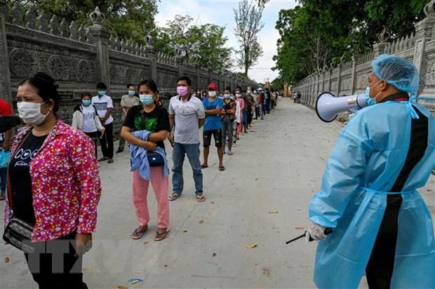 Binh sỹ quân đội Campuchia hướng dẫn người dân giữ khoảng cách phòng lây nhiễm COVID-19 tại một điểm tiêm chủng ở Phnom Penh. (Ảnh: AFP/TTXVN)