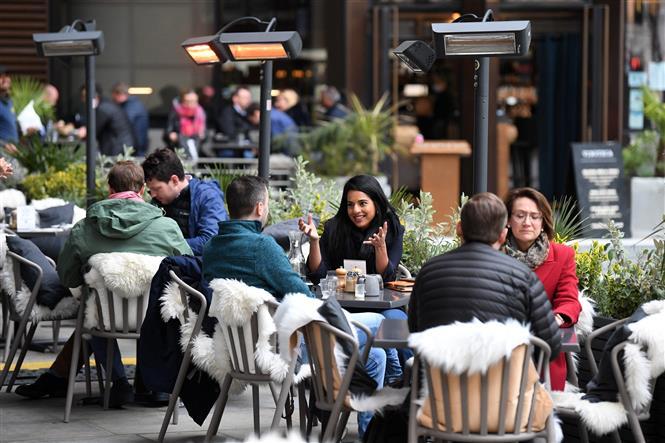 Người dân dùng bữa bên ngoài của một nhà hàng ở London, Anh ngày 29-4-2021. Ảnh: AFP/TTXVN