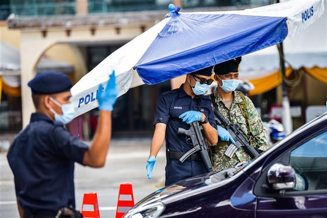 Cảnh sát và binh sĩ kiểm tra các phương tiện để phòng dịch COVID-19 tại Kuala Lumpur, Malaysia, ngày 1-6-2021. Ảnh: THX/ TTXVN