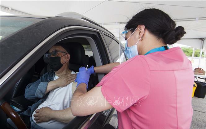 Nhân viên y tế tiêm vaccine phòng COVID-19 cho người dân tại Toronto, Canada, ngày 22-5-2021. Ảnh: THX/TTXVN