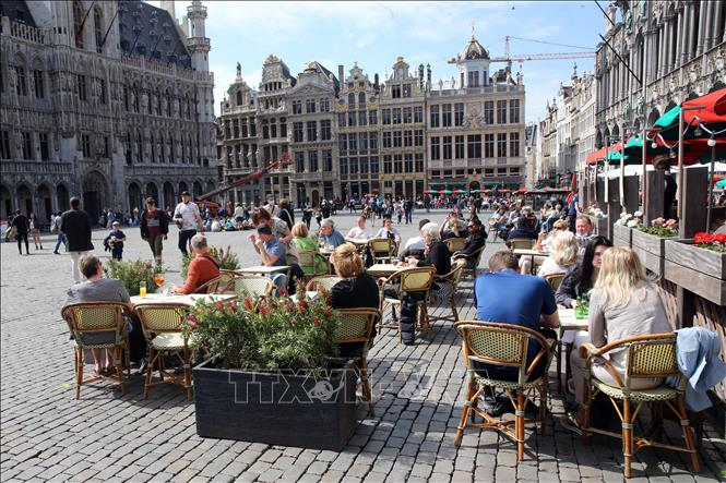 Người dân thưởng thức đồ uống bên ngoài một nhà hàng ở Brussels, Bỉ, ngày 9-5-2021. Ảnh: AFP/TTXVN