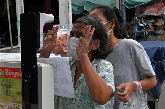 Đo thân nhiệt nhằm ngăn ngừa sự lây lan của dịch COVID-19 trước khi vào chợ tại Phnom Penh, Campuchia, ngày 24-5-2021. Ảnh: AFP/TTXVN