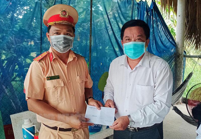 Phó bí thư Thường trực Huyện ủy tặng quà cho cán bộ, chiến sĩ và nhân viên y tế chốt kiểm soát khu vực cầu Cổ Chiên. Ảnh: Ngọc Vũ