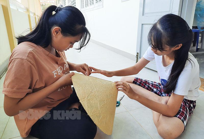 Các em học sinh thực hiện công đoạn làm nón từ nguyên liệu giấy dừa. Ảnh: CTV