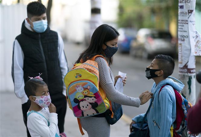 Phụ huynh đưa các em nhỏ đến lớp trở lại sau một thời gian dài thực hiện giãn cách xã hội do dịch COVID-19 tại Mexico City, Mexico ngày 7-6-2021. Ảnh: THX/TTXVN