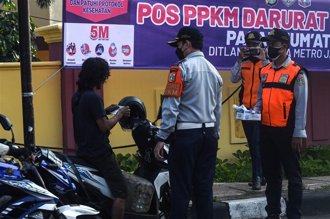 Nhân viên Bộ giao thông phát khẩu trang cho người dân để phòng tránh lây nhiễm COVID-19 tại Jakarta, Indonesia, ngày 3-7-2021. Ảnh: THX/TTXVN