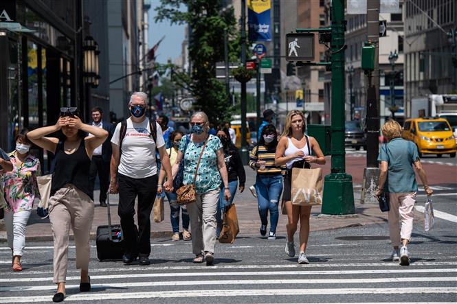 Người dân di chuyển trên một tuyến phố ở New York, Mỹ. Ảnh: AFP/TTXVN