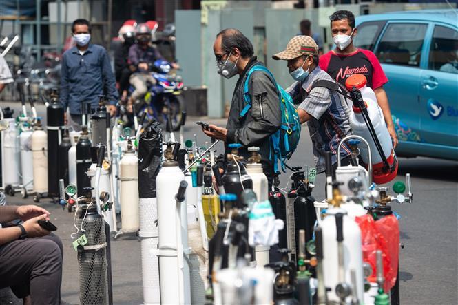 Người dân chờ nạp đầy bình oxy để cung cấp cho bệnh nhân COVID-19 tại Jakarta, Indonesia, ngày 5-7-2021. Ảnh: THX/ TTXVN