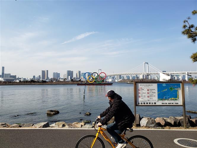 Một người Nhật Bản đạp xe qua biểu tượng Olympic ở Odaiba. Ảnh: Đào Thanh Tùng-PV TTXVN tại Nhật Bản