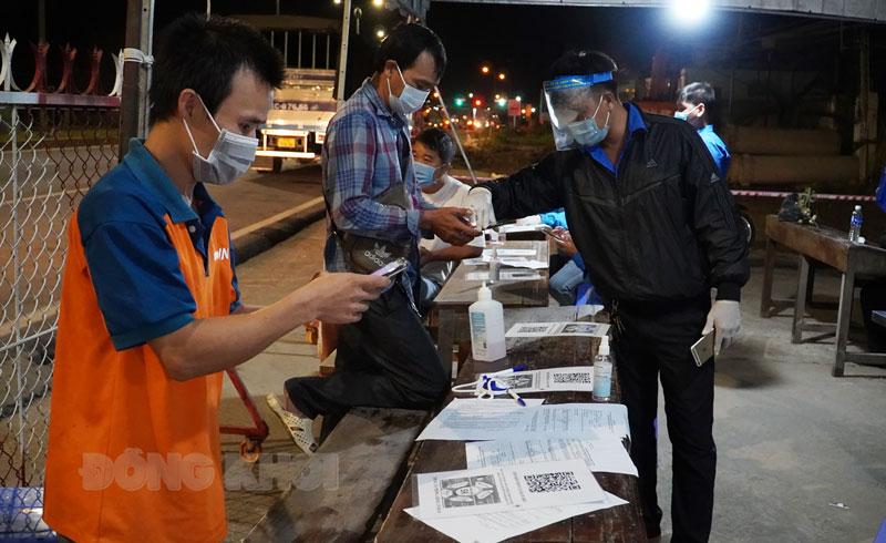 Người dân khai báo y tế trên ứng dụng Vietnam Health Declaration tại chốt cầu Rạch Miễu. Ảnh: Phan Hân