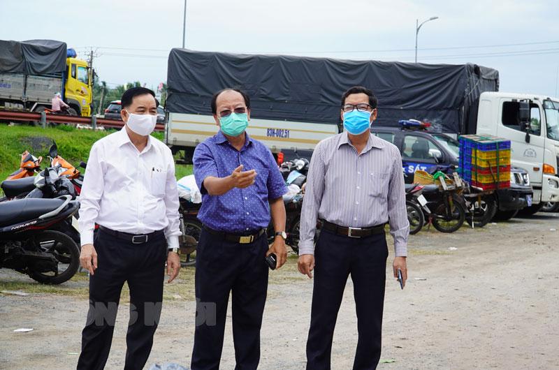 Chủ tịch UBND tỉnh Trần Ngọc Tam (bìa trái) kiểm tra tại điểm test nhanh Covid-19 tại cầu Rạch Miễu. Ảnh: Phan Hân