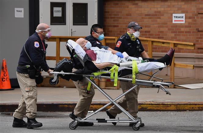 Nhân viên y tế chuyển bệnh nhân COVID-19 vào một bệnh viện ở New York City, Mỹ. Ảnh: AFP/TTXVN