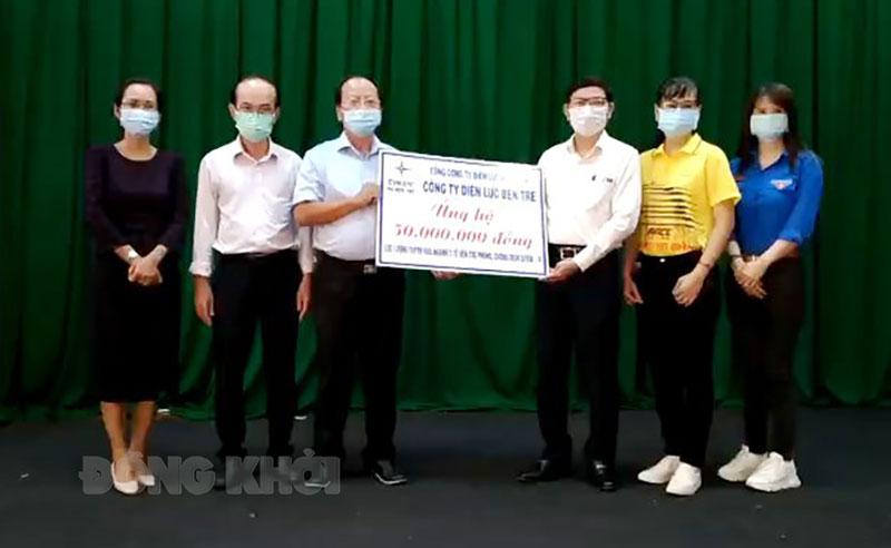 Đại diện Ban giám đốc Công ty Điện lực, Ban giám đốc Sở Y tế trao nhận biểu trưng đóng góp ủng hộ.