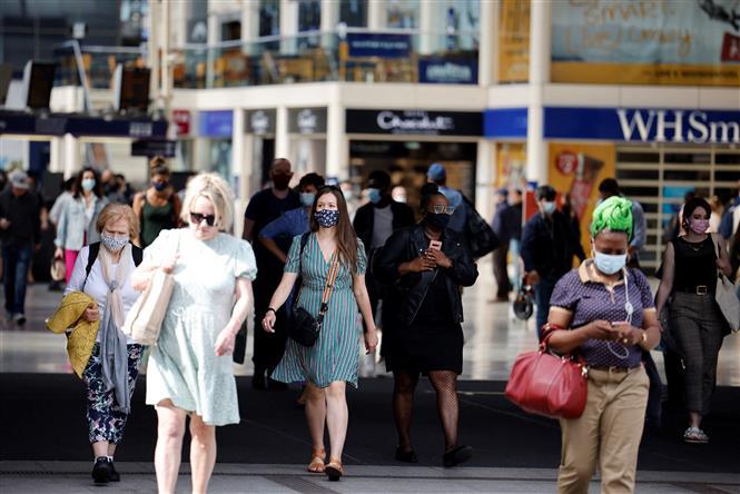 Người dân di chuyển trên đường phố tại London, Anh, ngày 7-6-2021. Ảnh: AFP/ TTXVN