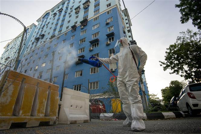 Nhân viên phun khử khuẩn nhằm ngăn dịch COVID-19 lây lan tại Kuala Lumpur, Malaysia ngày 23-7-2021. Ảnh: THX/TTXVN