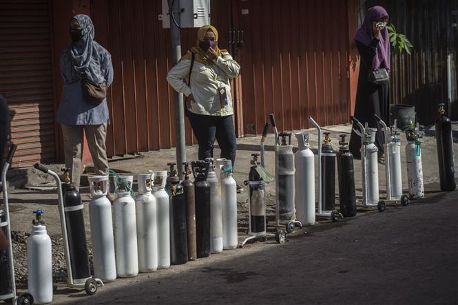 Người dân xếp hàng chờ bơm oxy y tế phục vụ điều trị cho bệnh nhân COVID-19 tại thành phố Surabaya, Đông Java, Indonesia, ngày 15-7-2021. Ảnh: AFP/TTXVN