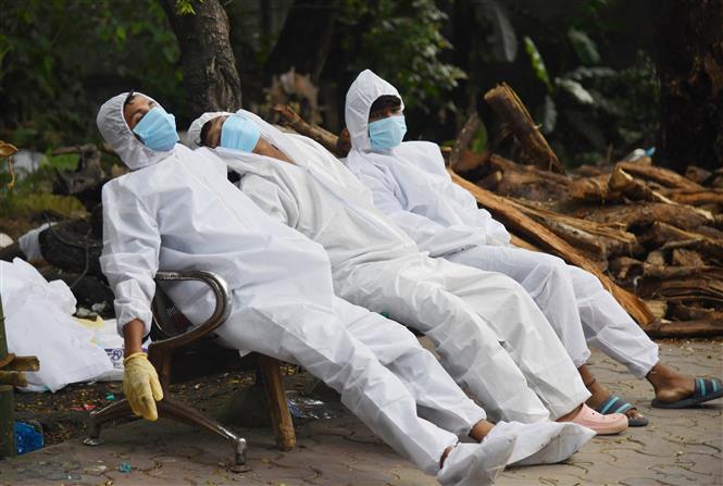 Nhân viên cấp cứu nghỉ tạm trên ghế băng sau một ngày bận rộn vì vận chuyển bệnh nhân COVID-19 tại Guwahati, Ấn Độ ngày 25-6-2021. Ảnh: AFP/TTXVN