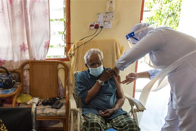 Nhân viên y tế tiêm vaccine ngừa COVID-19 cho người dân tại Selangor, Malaysia ngày 21-7-2021. Ảnh: THX/TTXVN