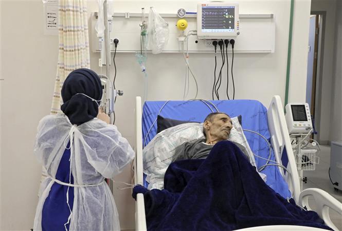 Nhân viên y tế điều trị cho bệnh nhân COVID-19 tại Tây Hebron, Khu Bờ Tây ngày 30-5-2021. Ảnh: AFP/TTXVN