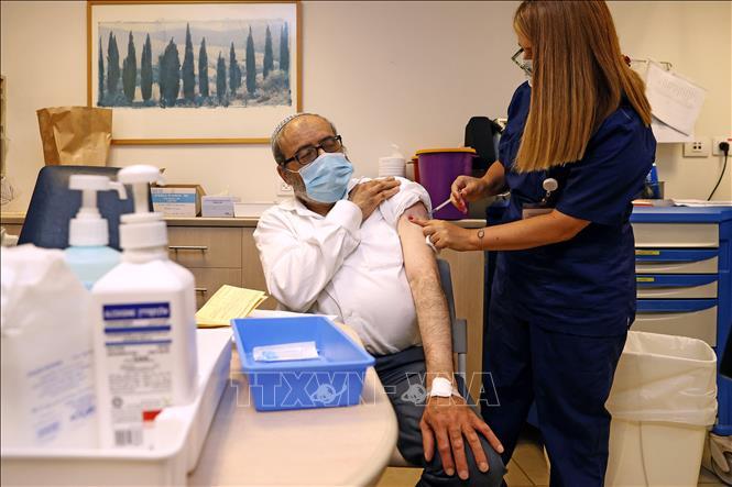 Nhân viên y tế tiêm vaccine COVID-19 cho người dân tại Tel Aviv, Israel. Ảnh: AFP/TTXVN