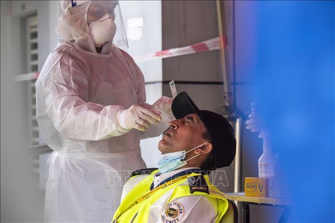Nhân viên y tế lấy mẫu xét nghiệm COVID-19 cho người dân tại Selangor, Malaysia ngày 15-7-2021. Ảnh: THX/TTXVN