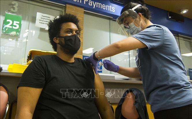 Nhân viên y tế tiêm vaccine ngừa COVID-19 cho người dân tại Toronto, Canada ngày 24-7-2021. Ảnh: THX/TTXVN