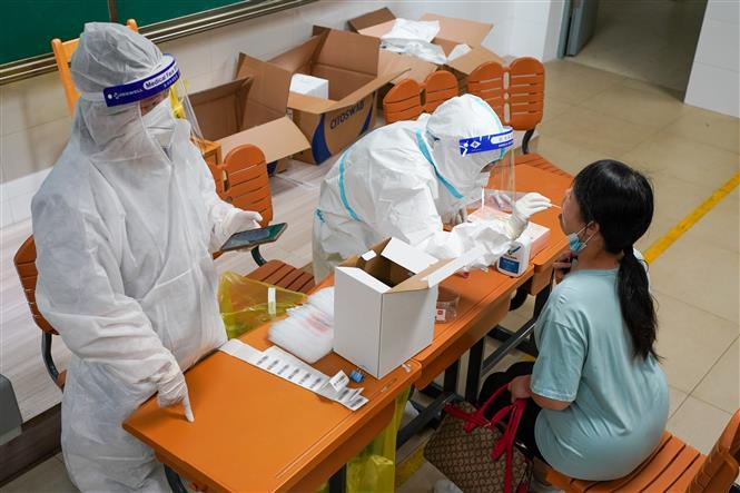 Nhân viên y tế lấy mẫu xét nghiệm COVID-19 cho người dân tại Nam Kinh, tỉnh Giang Tô, Trung Quốc, ngày 25-7-2021. Ảnh: THX/TTXVN
