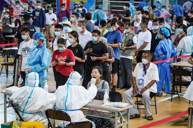 Nhân viên y tế lấy mẫu xét nghiệm COVID-19 cho người dân tại Nam Kinh, tỉnh Giang Tô, Trung Quốc, ngày 22-7-2021. Ảnh: THX/ TTXVN