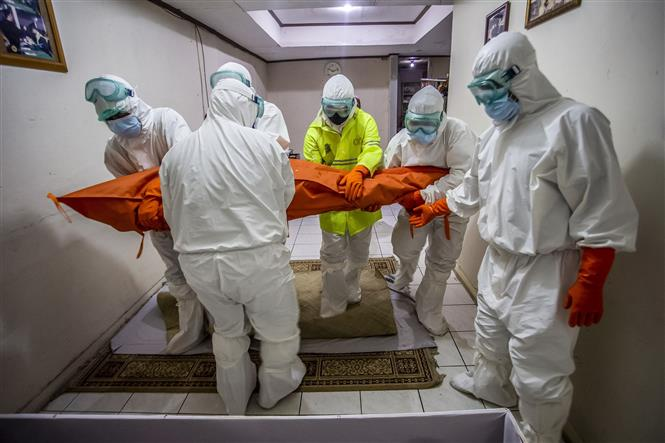 Lực lượng chức năng chuyển thi thể bệnh nhân COVID-19, sau khi người bệnh tự cách ly tại nhà do bệnh viện quá tải ở Bogor, Tây Java, Indonesia, ngày 6-7-2021. Ảnh: AFP/TTXVN