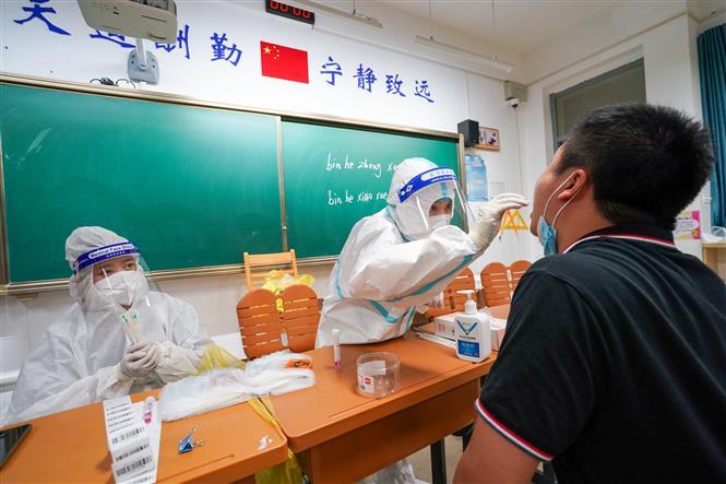 Nhân viên y tế lấy mẫu xét nghiệm COVID-19 tại Nam Kinh, Trung Quốc, ngày 25-7-2021. Ảnh: THX/TTXVN