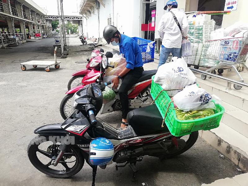 Shipper Xanh đi giao hàng cho người dân.