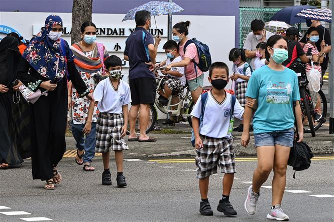 Người dân đeo khẩu trang phòng dịch COVID-19 tại Singapore. Ảnh: AFP/TTXVN
