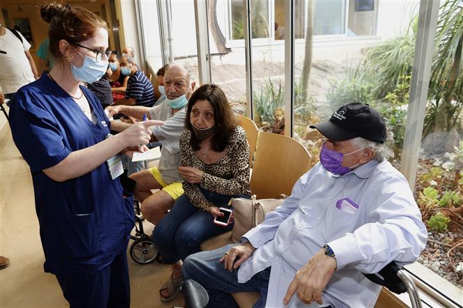 Người dân xếp hàng chờ tiêm vaccine Pfizer phòng COVID-19 tại Tel Aviv, Israel, ngày 12-7-2021. Ảnh: AFP/ TTXVN