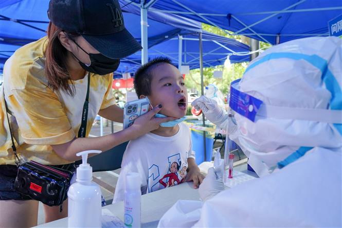 Nhân viên y tế lấy mẫu xét nghiệm COVID-19 cho người dân tại thành phố Nam Kinh, tỉnh Giang Tô, Trung Quốc ngày 29-7-2021. Ảnh: THX/TTXVN