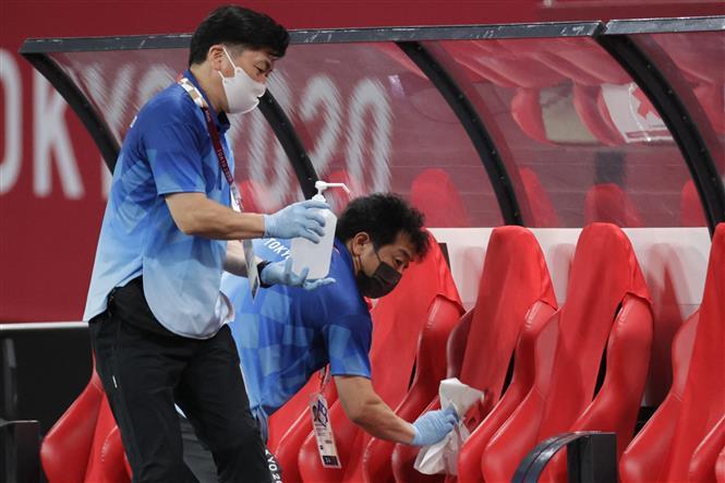 Nhân viên khử trùng ghế ngồi tại sân vận động ở Sapporo, Nhật Bản sau khi kết thúc một trận đấu bóng đá Olympic Tokyo 2020, ngày 22-7-2021. Ảnh: AFP/TTXVN
